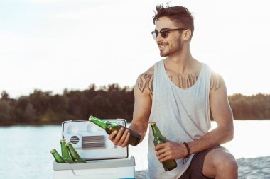 Young casual man in sunglasses holding bottles of beer on riverside stock vector