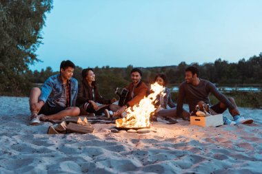friends resting near campfire on sandy beach