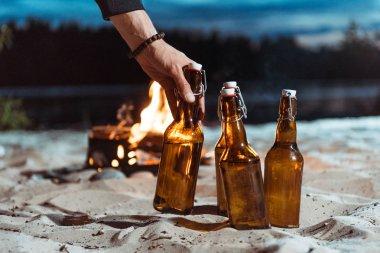 human hand taking bottle of beer