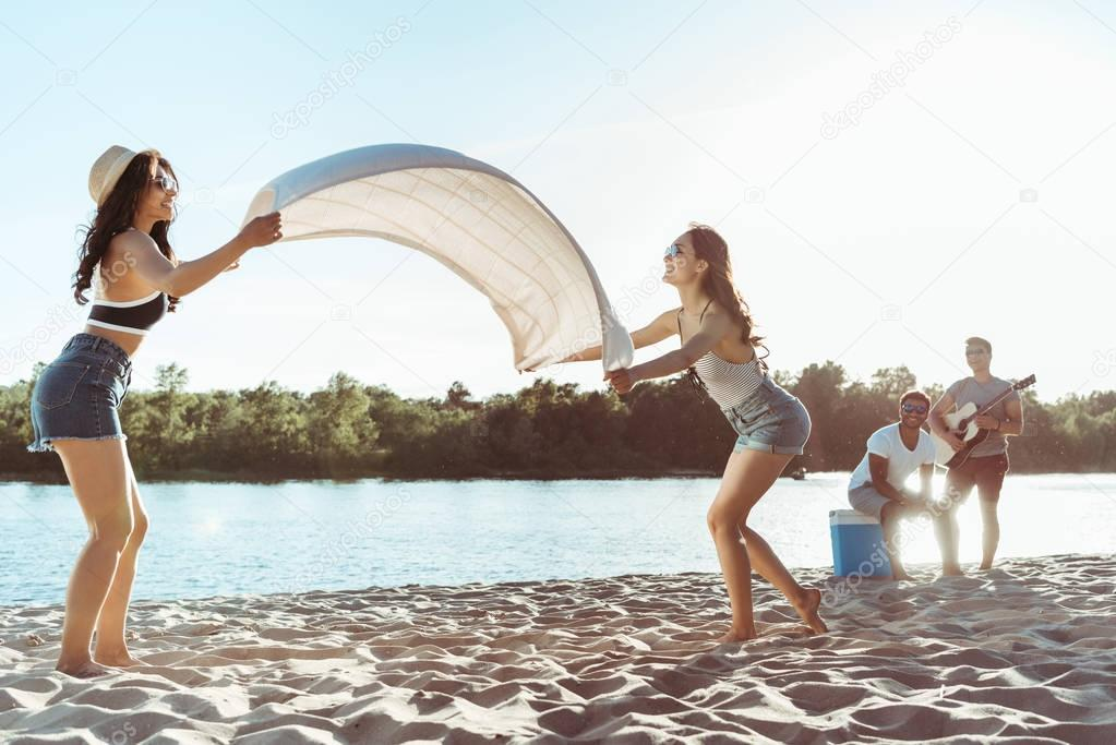girls waving beach blanket on riverside