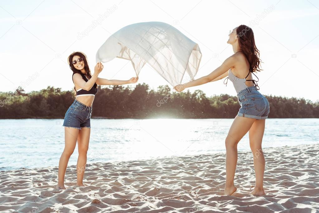 girls waving beach blanket on riverside