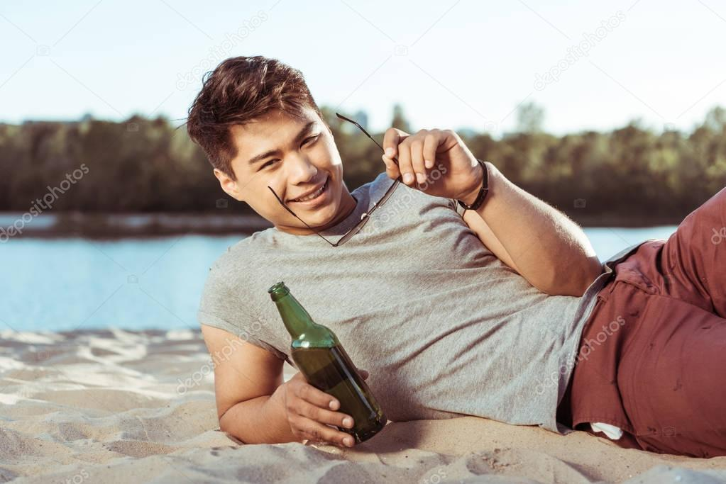 man lying on beach with bottle of beer