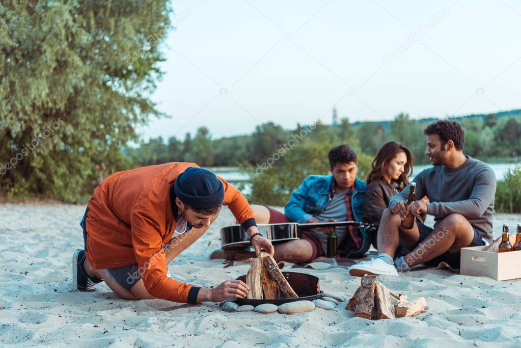 friends trying to make bonfire on beach