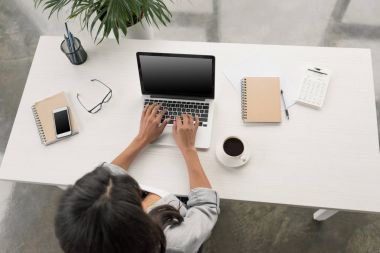 Businesswoman using laptop while sitting at workplace