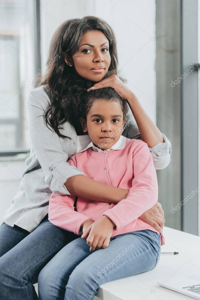 African american mother hugging daughter