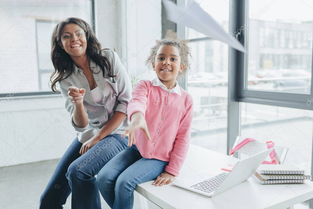 Daughter with mother throwing paper airplane