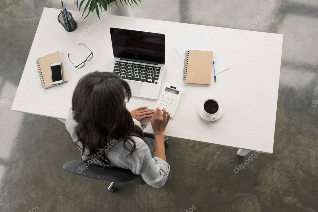 businesswoman using calculator on workplace