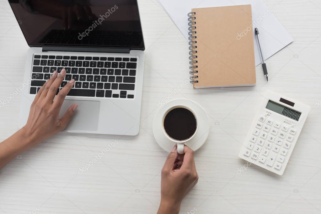 businesswoman working on laptop and drinking coffee