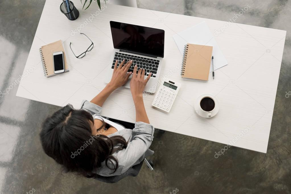 businesswoman typing on laptop while sitting at workplace