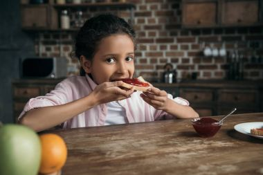 girl eating toast with jam