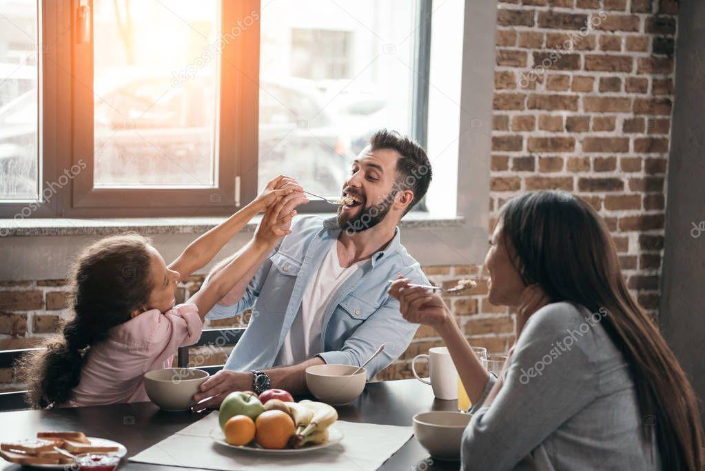 girl feeding father with porridge