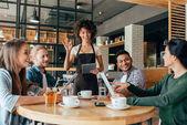 Kellnerin nimmt Bestellungen von Kunden entgegen