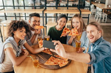 Young man taking selfie with multiethnic friends having pizza in cafe stock vector