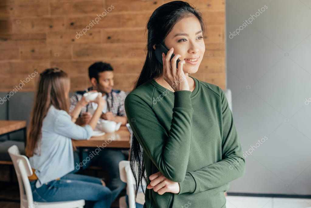 Asian woman talking on smartphone in cafe