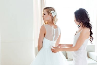 bridesmaid dressing up bride