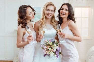 bride with bridesmaids drinking champagne