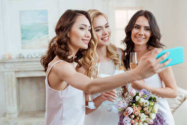 bride with bridesmaids taking selfie