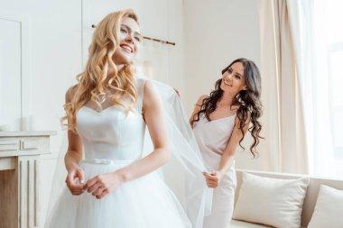Happy beautiful bridesmaid preparing bride for wedding ceremony stock vector