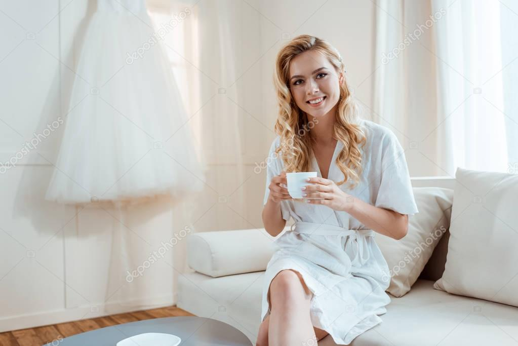 woman drinking coffee on sofa