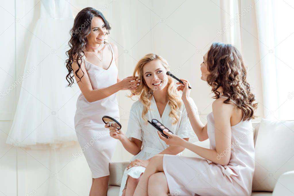 bridesmaids preparing bride for ceremony