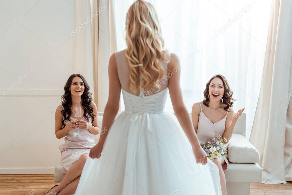 excited bridesmaids looking at bride