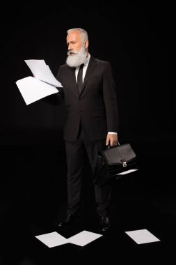 businessman holding papers and briefcase