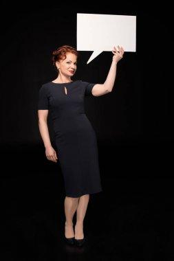 Full-length shot of woman in black dress holding a blank speech bubble near her head stock vector