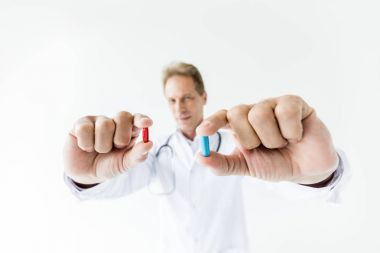 Close-up view of doctor holding blue and red pills isolated on white stock vector
