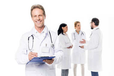 Cheerful middle aged doctor with stethoscope and clipboard looking at camera while colleagues standing behind, isolated on white stock vector