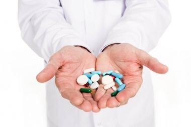 Close-up partial view of doctor holding various pills isolated on white stock vector