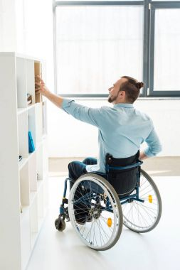 disabled businessman reaching to shelf