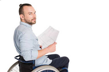 Disabled architect in wheelchair looking at camera while holding blueprints, isolated on white stock vector
