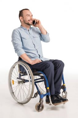 man in wheelchair talking on smartphone