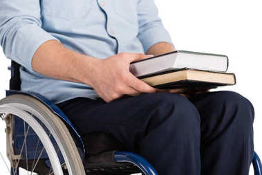 man on wheelchair holding books