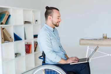businessman in wheelchair working with laptop
