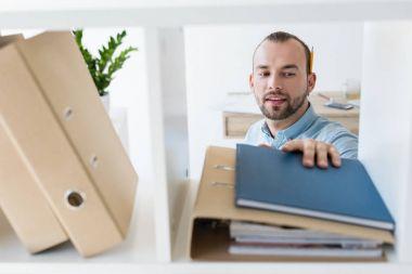 businessman reaching for paperwork on shelf