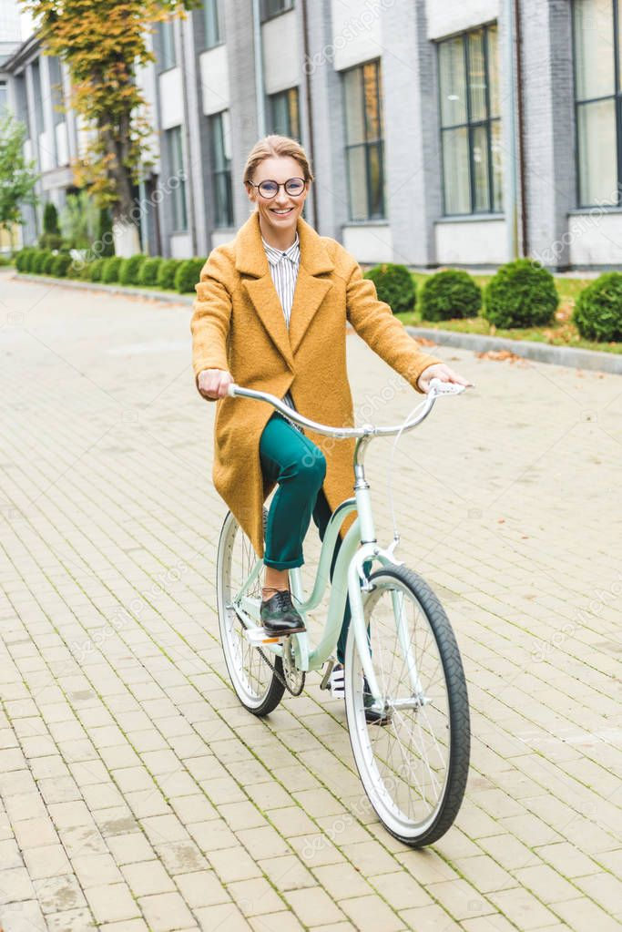 cheerful woman riding bicycle