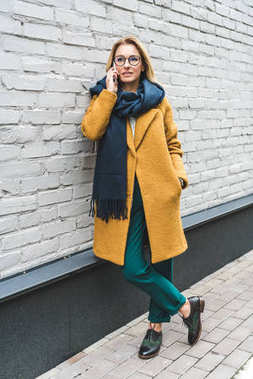woman in yellow coat with smartphone