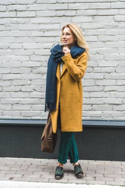 pensive woman in yellow coat