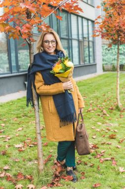 stylish woman with flowers in autumn park