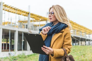 businesswoman with clipboard working on construction
