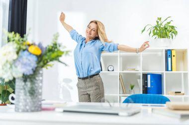businesswoman stretching in modern office
