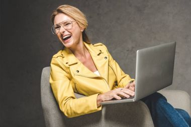 laughing woman using laptop