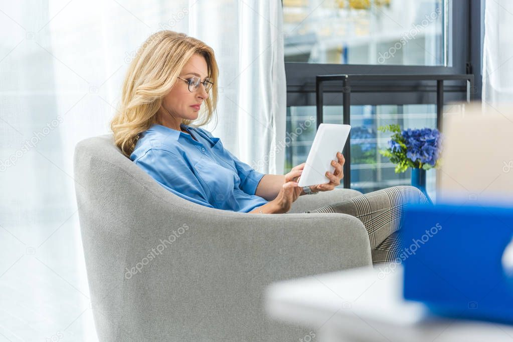 businesswoman with tablet on armchair