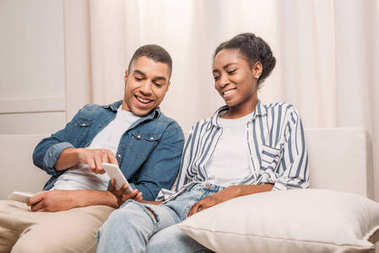 african american couple sitting with smartphones