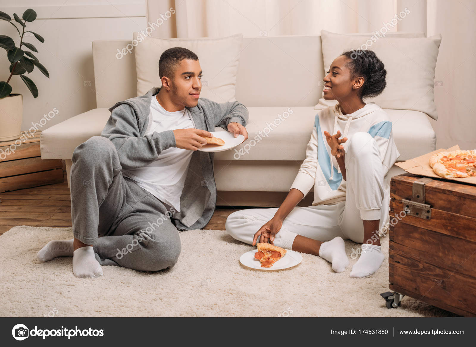 Eating Pizza Beside Sofa Stock Photo