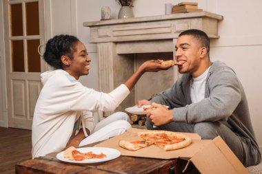 woman feeding man pizza