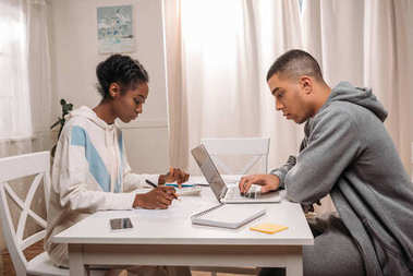 couple using laptop and calculator