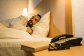 Photo bearded mature man in bathrobe sleeping in hotel room