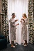 Fotografie boční pohled šťastné dospělý pár v župany pití kávy a usmívá se navzájem v hotelovém pokoji